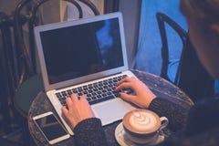 在膝上型计算机键盘的女性手在咖啡店 免版税库存图片