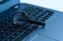 在膝上型计算机键盘的放大镜在蓝色口气 免版税库存图片