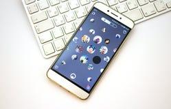 在膝上型计算机键盘的智能手机开放apps Nimses应用 库存照片