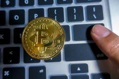 在膝上型计算机键盘的金黄Bitcoin有指点的输入 免版税库存照片