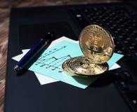 在膝上型计算机键盘的金黄Bitcoin硬币 以图表的形式企业笔记 库存照片