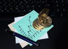 在膝上型计算机键盘的金黄Bitcoin硬币 以图表的形式企业笔记 免版税图库摄影