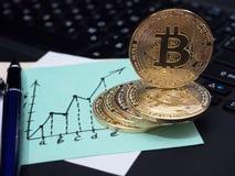 在膝上型计算机键盘的金黄Bitcoin硬币 以图表的形式企业笔记 库存图片