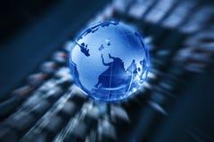在膝上型计算机键盘的玻璃地球 免版税库存图片