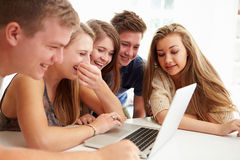 在膝上型计算机附近一起被会集的小组少年 库存照片