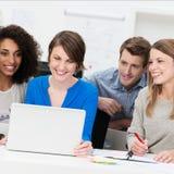 在膝上型计算机附近被编组的微笑的企业队 免版税库存图片