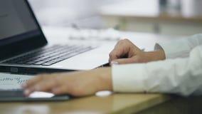 在膝上型计算机,采取智能手机的女性手的妇女键入的电子邮件对检查消息 股票视频