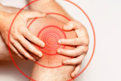 在膝盖关节的剧痛,特写镜头 颜色图象,在白色背景 红颜色痛苦地区  免版税图库摄影
