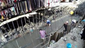 在膝盖深排水设备污水运河浸没的工作者修理它 股票录像