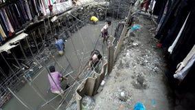 在膝盖深排水设备污水运河浸没的工作者修理它 影视素材