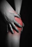 在膝盖的痛苦。做在病的膝盖的按摩医生按摩在红色 免版税库存图片
