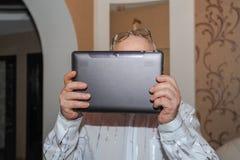 在膝部、计划和预定的退休旅行,特写镜头的年长人藏品片剂 使用一种片剂在他的房子里 库存图片