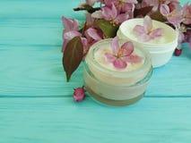 在自创木的背景的奶油色化妆润湿的疗法萃取物再生产品秀丽木兰花 库存图片