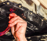 在自动传输的换油 填装油通过水管 汽车维护驻地 红色齿轮油 加州的手 图库摄影