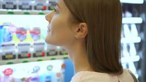 在自动售货机外面的美好的饥饿的妇女采摘项目在购物中心 选择不健康的快餐饿 股票视频