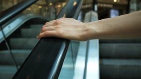 在自动扶梯扶手栏杆的女孩的手在购物中心,特写镜头 图库摄影