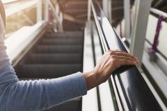 在自动扶梯扶手栏杆的妇女的右手 库存图片