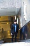 在自动扶梯的幼小亚洲公商业主管 免版税图库摄影