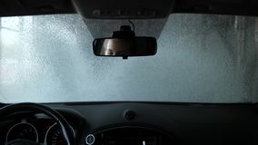 在自动洗车的汽车 从客舱的射击 在镜子是妇女司机的眼睛 r 股票录像