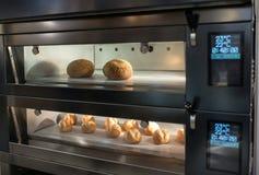 在自动烤箱的烘烤面包 免版税库存图片