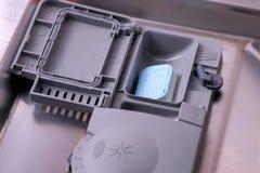 在自动隔间的洗涤剂片剂在洗碗机 图库摄影
