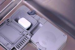 在自动隔间的洗涤剂片剂在洗碗机 库存图片