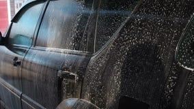 在自助洗车的洗车过程 水喷气机与高压的洗涤从汽车的泡沫 端 影视素材