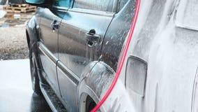 在自助洗车的洗车过程 水喷气机与高压的洗涤从汽车的泡沫 端 股票录像