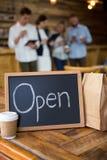 在自助食堂打开与一次性咖啡杯和纸袋的牌 库存图片