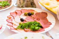 在自助餐的一块板材显示的可口熏制的火腿和开胃菜服务在党或招待会 免版税库存图片