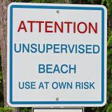 在自己的风险标志的注意未加监督的海滩用途 免版税库存照片