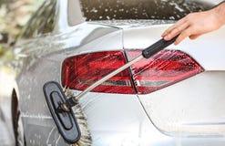 在自已服务手工洗车洗车的银色尾灯和后面 刷子清理香波报道的表面 免版税库存照片