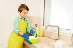 在自来水下的孩子男孩洗涤的盘 免版税库存照片