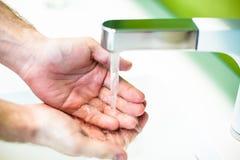 在自来水下的洗涤的手 免版税图库摄影