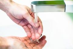 在自来水下的洗涤的手 免版税库存照片
