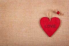 在自然亚麻制背景的红色木心脏垂饰 自然本底的木华伦泰 背景和纹理 库存图片