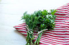 在自然亚麻布餐巾的绿色荷兰芹和莳萝叶子在木背景 库存照片