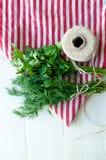 在自然亚麻布餐巾的绿色荷兰芹和莳萝叶子在木背景 免版税库存图片