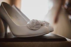 在自然光的典雅的白色婚礼鞋子从 图库摄影