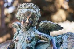 在自然公园backgorund的雕象小天使 免版税库存照片