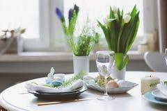 在自然土气样式的蓝色和白色口气装饰的复活节和春天欢乐桌,用鸡蛋,兔宝宝,鲜花 库存图片