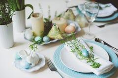 在自然土气样式的蓝色和白色口气装饰的复活节和春天欢乐桌,用鸡蛋,兔宝宝,鲜花 免版税图库摄影