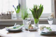 在自然土气样式的蓝色和白色口气装饰的复活节和春天欢乐桌,用鸡蛋,兔宝宝,鲜花 免版税库存图片