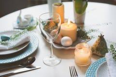 在自然土气样式的蓝色和白色口气装饰的复活节和春天欢乐桌,用鸡蛋,兔宝宝,鲜花 库存照片