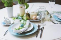 在自然土气样式的蓝色和白色口气装饰的复活节和春天欢乐桌,用鸡蛋,兔宝宝,鲜花 免版税库存照片