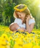 在自然有黄色流程的绿色草甸照顾喂养她的婴孩 免版税库存照片