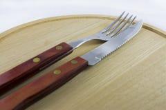 在自然木头盘的银器  免版税图库摄影