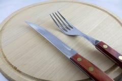 在自然木头盘的银器  免版税库存照片