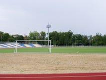 在自然本底的鲜绿色的橄榄球场 与门、下端背面和塑料位子的一个现代橄榄球场 免版税图库摄影