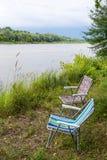 在自然的两把折叠椅,在河的河岸 库存照片